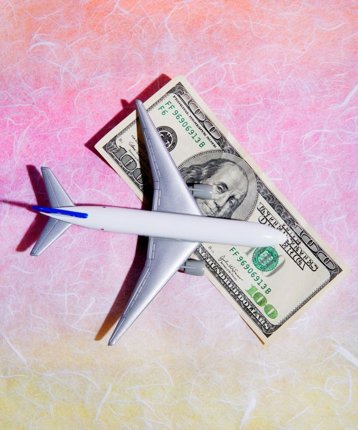 airplane over a dollar bill  - low budget traveling